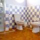 Baño con suelo de baldosa en diagonal, enmarcada en azulejo blanco